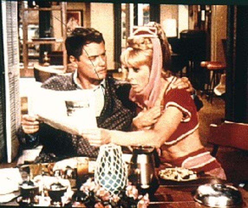 Jeannie (Barbara Eden, r.) zaubert für Tony (Larry Hagman, l.) ein Zeitungsexemplar mit dem Datum vom nächsten Tag herbei, da ihr Roger den falschen...