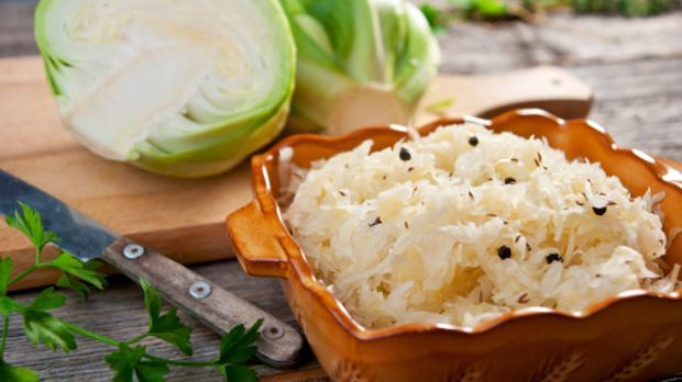 Zubereitetes Sauerkraut in einer braunen Schüssel, im Hintergrund ein halber...