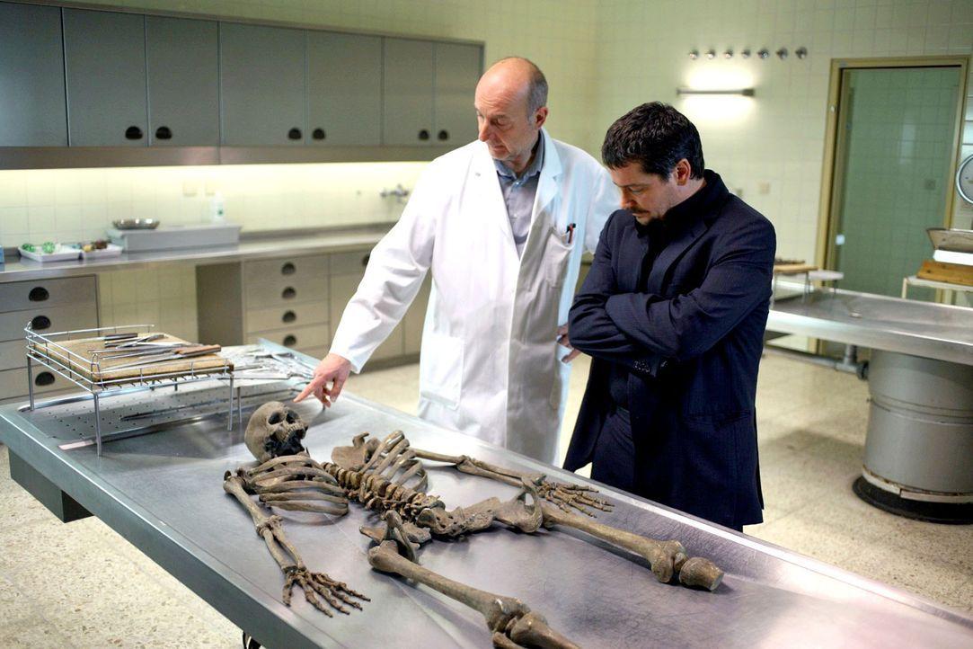 Keller (Fritz Karl, r.) und der Gerichtsmediziner (Michael Schönborn, l.) untersuchen das gefundene Skelett. - Bildquelle: Petro Domenigg Sat.1