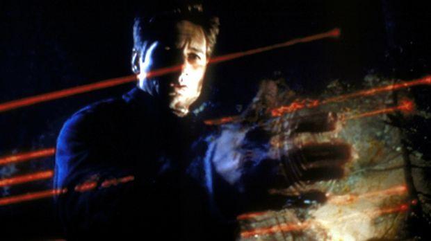 Mulder (David Duchovny) versucht mit Hilfe von Laserstrahlen, ein in den Wäld...