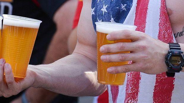 Ein Mann gekleidet in Stars and Stripes hält zwei Plastikbecher mit Bier