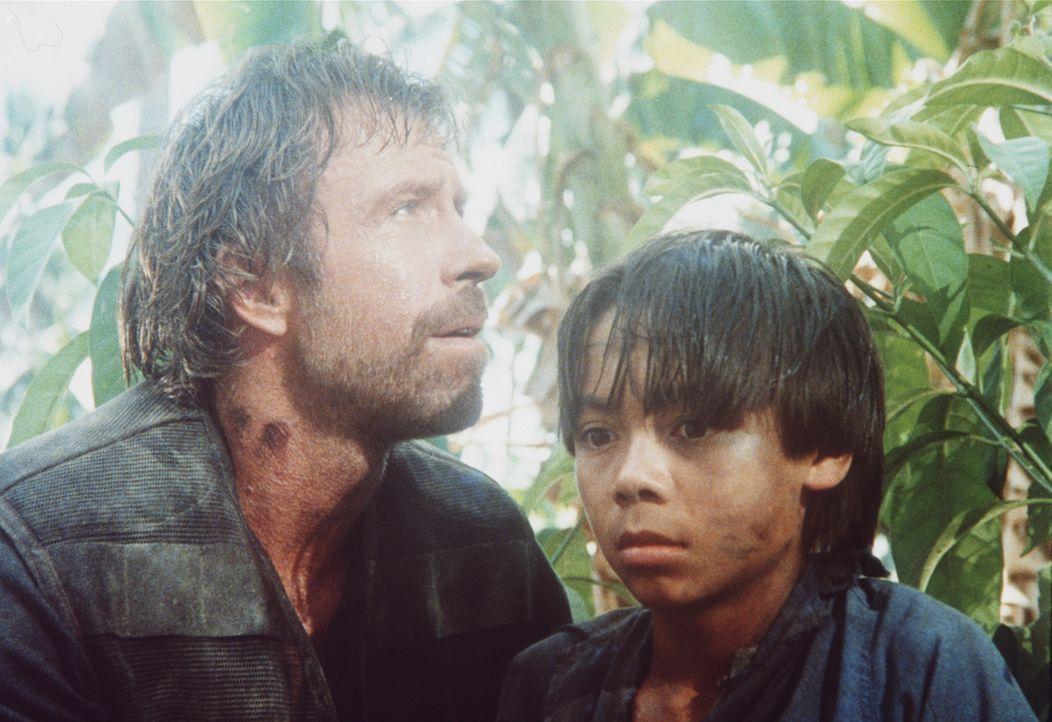 Braddock (Chuck Norris, l.) flieht mit seinem Sohn Van (Roland Harrah III., r.) durch den Dschungel ... - Bildquelle: Cannon Films