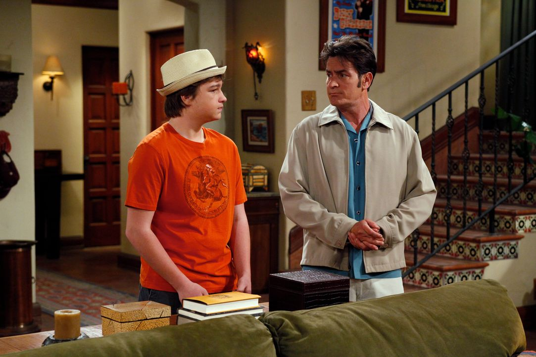 Jake (Angus T. Jones, l.) chauffiert seinen Onkel Charlie (Charlie Sheen, r.), weil der betrunken ist. Charlie drängt seinen Neffen, über eine rote... - Bildquelle: Warner Brothers