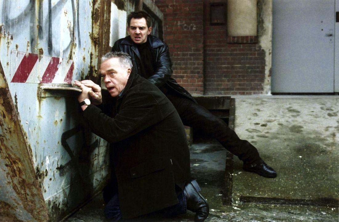 Wolff (Jürgen Heinrich, l.) und Tom (Steven Merting, r.) verfolgen das Auto des flüchtenden Täters. - Bildquelle: Claudius Pflug Sat.1
