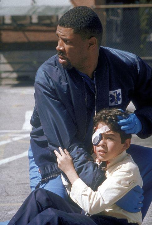 Benton (Eric La Salle, l.) hilft einem kleinen Jungen, der am Auge schwer verletzt ist. - Bildquelle: TM+  2000 WARNER BROS.