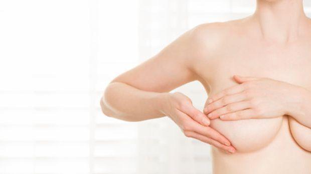 Frau tastet mit beiden Händen ihre Brust ab