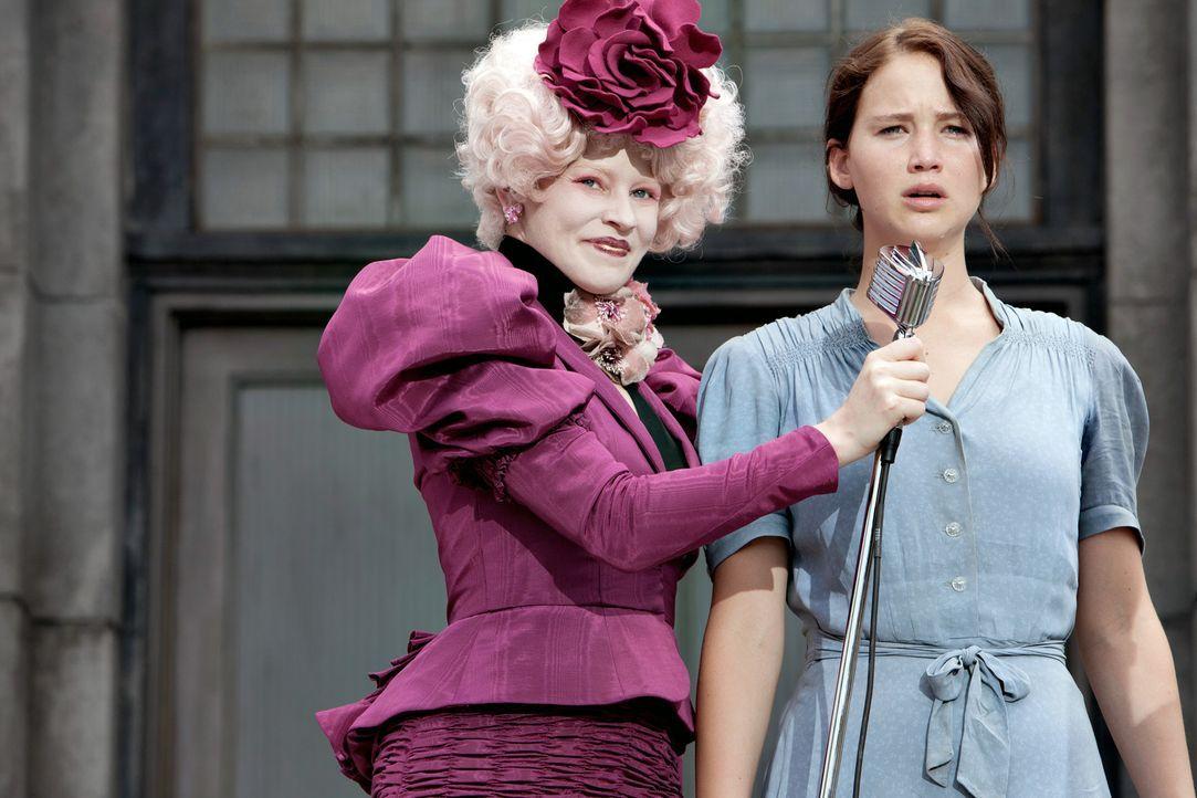 Kaum in der Arena angekommen, wird Katniss (Jennifer Lawrence, r.) von ihrer Betreuerin Effie Trinket (Elizabth Banks, l.) auf die Bühne gezogen. V... - Bildquelle: Studiocanal GmbH