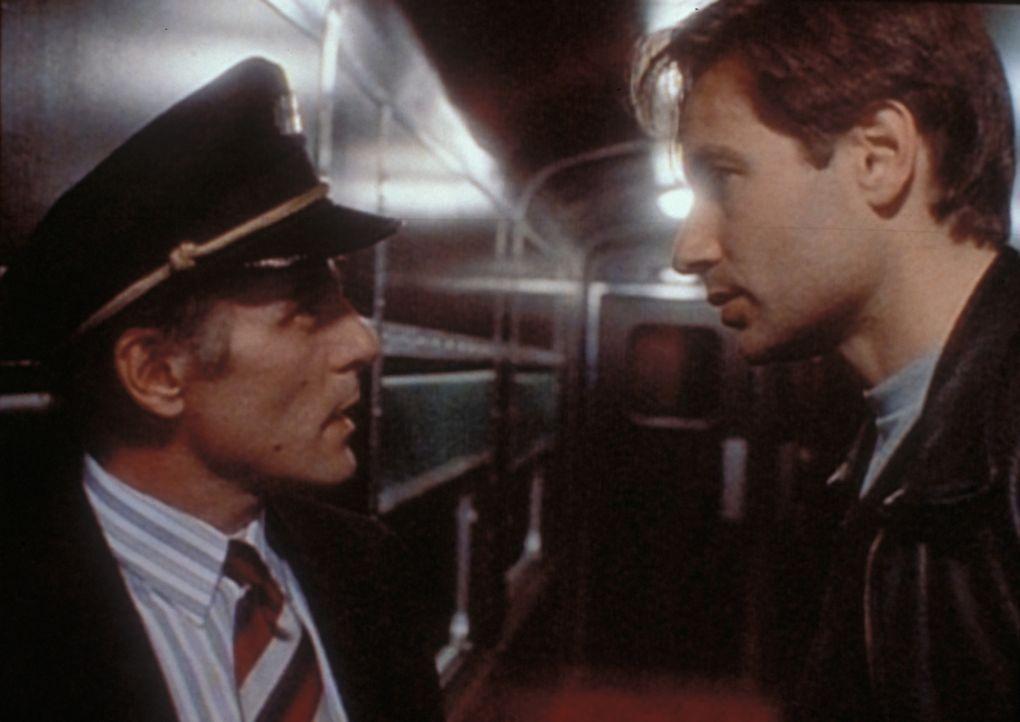 Mulder (David Duchovny, r.) will sich von eine Zugschaffner (l.) den Regierungswaggon öffnen lassen, in dem er einen Außerirdischen vermutet. - Bildquelle: TM +   2000 Twentieth Century Fox Film Corporation. All Rights Reserved.