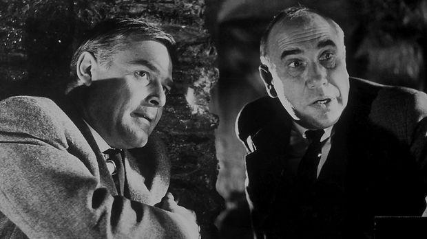 Inspektor Puddler (Charles Regnier, r.) von Scotland Yard steht vor einem Rät...