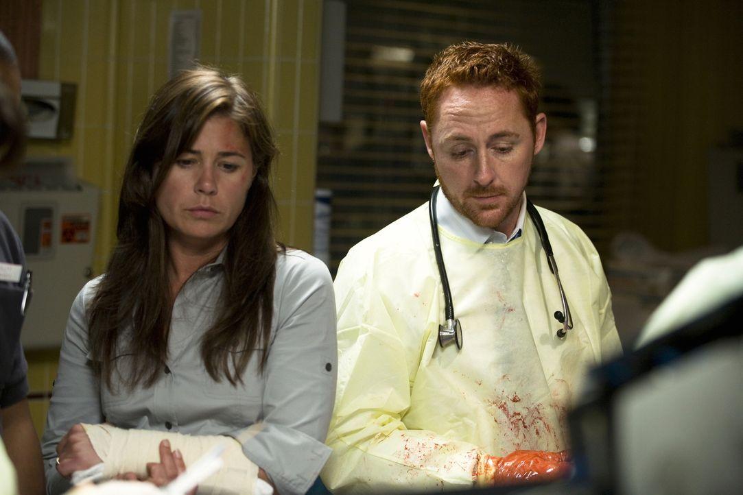 Abby (Maura Tierney, l.), die durch die Explosion des Krankenwagens nur leicht verletzt wurde, erfährt von Dr. Archie Morris (Scott Grimes, r.), da... - Bildquelle: Warner Bros. Television