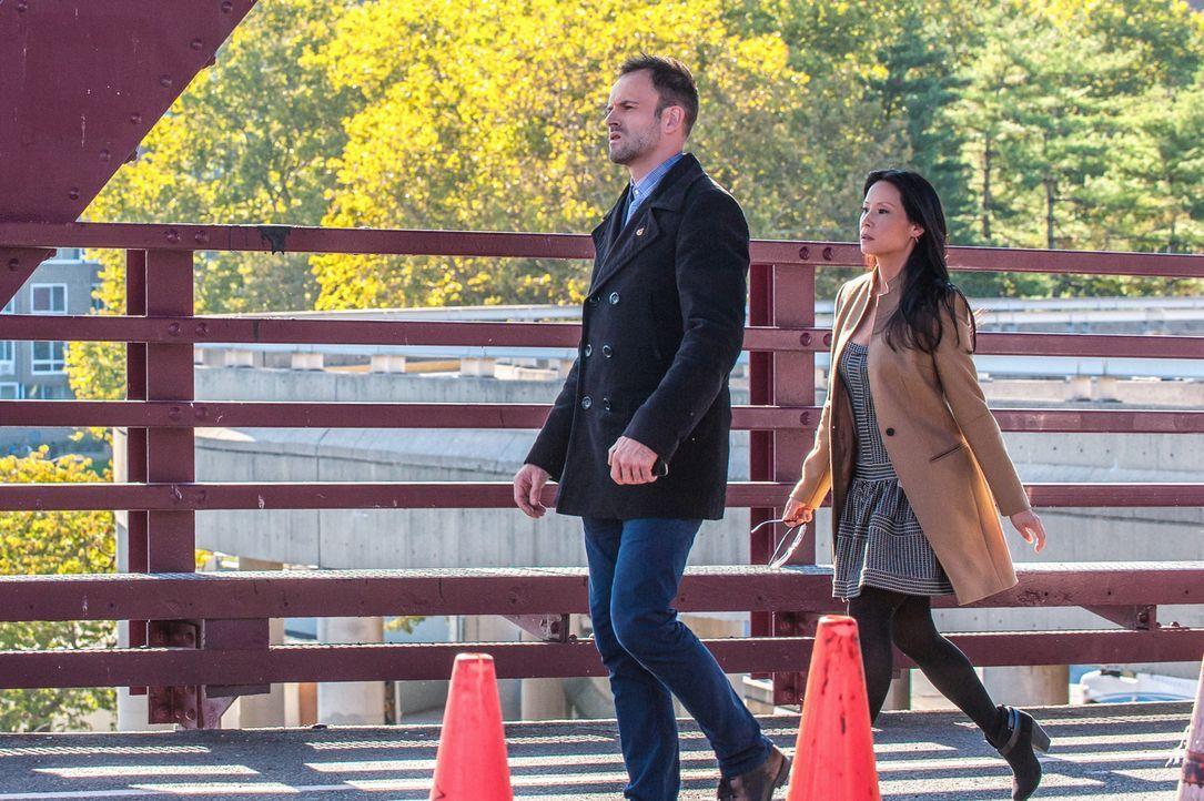 Sherlock Holmes (Jonny Lee Miller, l.) und Joan Watson (Lucy Liu, r.) werden zu einem Tatort auf einer Brücke gerufen, wo eine junge Frau erschossen... - Bildquelle: CBS Television