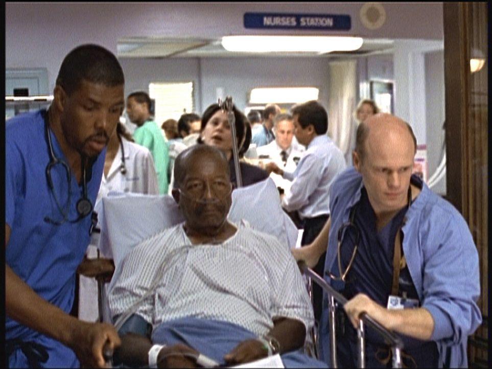 Zähneknirschend bringt Romano (Paul McCrane, r.) seinen Patienten Fletcher (Gerry Black, M.) in den OP, den er eigentlich abweisen wollte. Das hat i... - Bildquelle: TM+  2000 WARNER BROS.