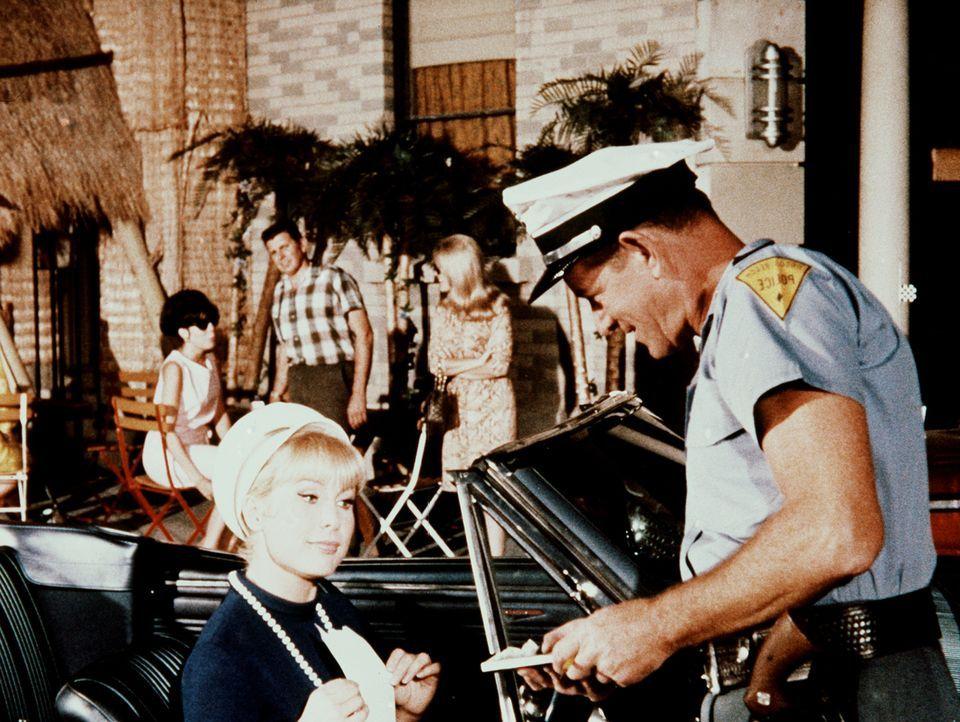Jeannie (Barbara Eden, l.) fährt mit Tonys Wagen verkehrt in eine Einbahnstraße und gerät deshalb mit einem Polizisten in Konflikt. - Bildquelle: Columbia Pictures