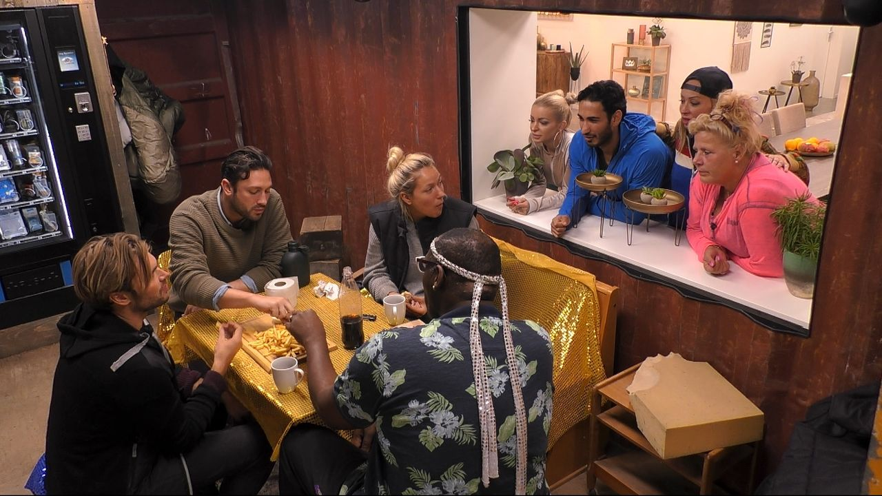 Tag11_Burgermenue14_Die Bewohner der Baustelle essen ihr Burgermenü und die Villa-Bewohner gucken zu und sind neidisch