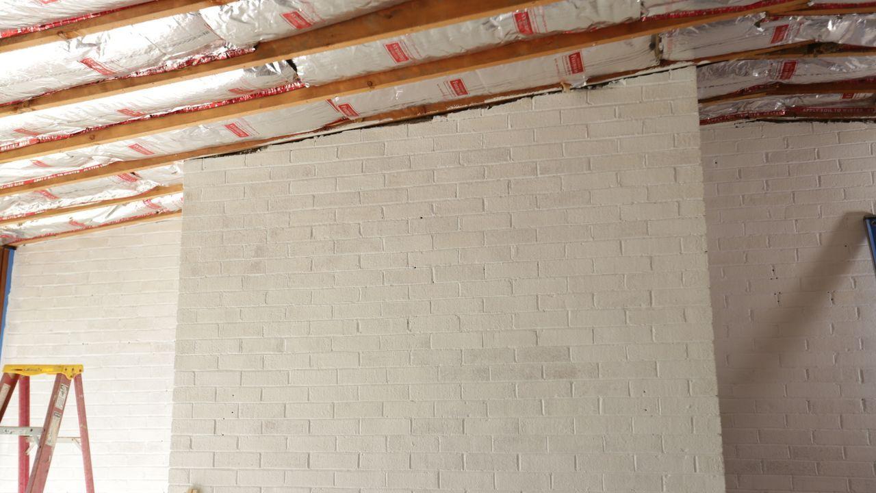 Die drückende, dunkle Decke soll weichen und durch einen weißen Anstrich der Ziegelwand ein hellerer, offener Wohnbereich geschaffen werden. - Bildquelle: 2016, Scripps Networks, LLC. All Rights Reserved.