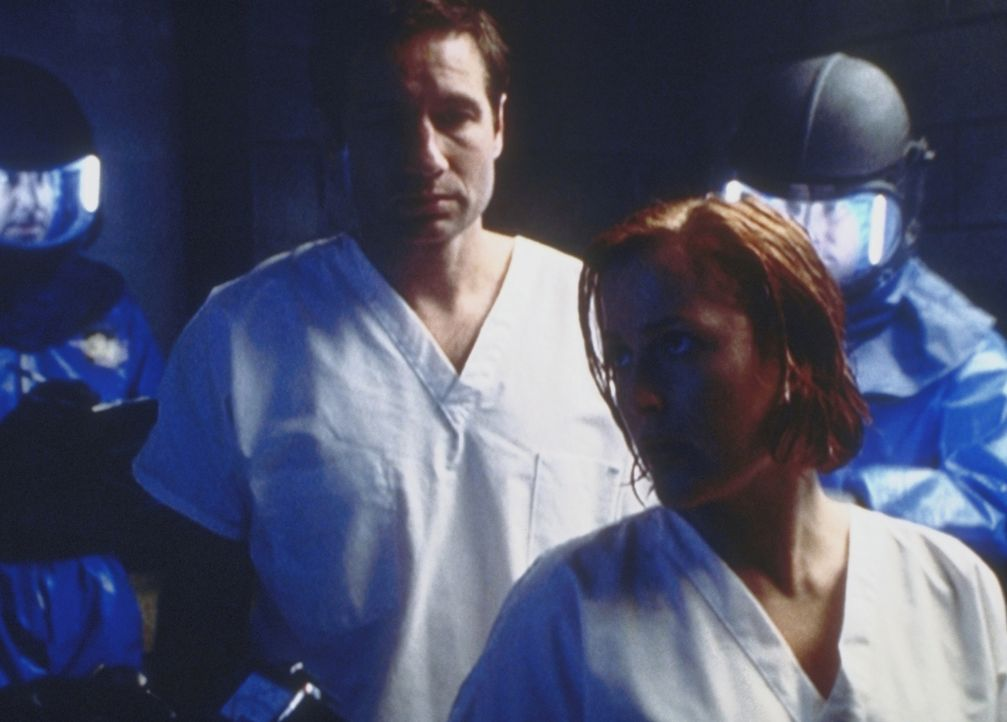 Mulder (David Duchovny, l.) und Scully (Gillian Anderson, r.) sind von angeblichen Mitarbeitern der Seuchenschutzbehörde verhaftet und in ein Militä... - Bildquelle: TM +   2000 Twentieth Century Fox Film Corporation. All Rights Reserved.