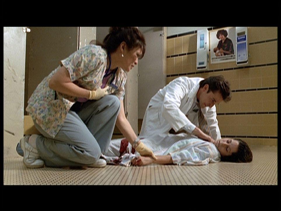 Dr. Carter (Noah Wyle, r.) kümmert sich um die schwangere Noni (Kimberly McCullough, liegend), die mit Unterleibskrämpfen blutend zusammengebrochen... - Bildquelle: TM+  2000 WARNER BROS.