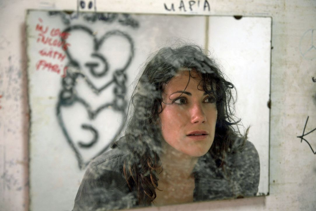 Claudia (Bettina Zimmermann) erstarrt vor Schreck, als sie im Spiegel einer maroden Tankstelle die Initialen C und G entdeckt. - Bildquelle: Sat.1