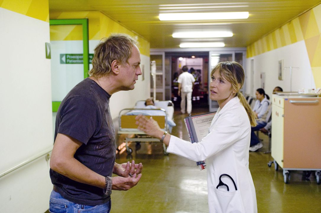 Zwischen Tür und Angel teilt Ellen (Anica Dobra, r.) Carlo (Uwe Ochsenknecht, l.) ihre Verdachtsdiagnose einer Herzinsuffizienz mit. - Bildquelle: Sat.1