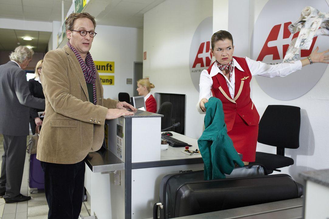 Ein Fluggast (Kai Lentrodt, l.) kommt mit einem schweren Koffer an den Check-In-Schalter im Flughafen. Die Schalterfrau (Anke Engelke, r.) öffnet un... - Bildquelle: Guido Engels SAT.1