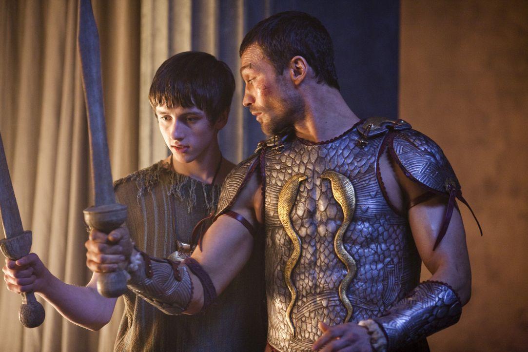 Magistrat Clavius besucht mit seinem Sohn Numerius (Lliam Powell, l.) die Gladiatorenschule, da Spartakus (Andy Whitfield, r.) dem Jungen Unterricht... - Bildquelle: 2010 Starz Entertainment, LLC