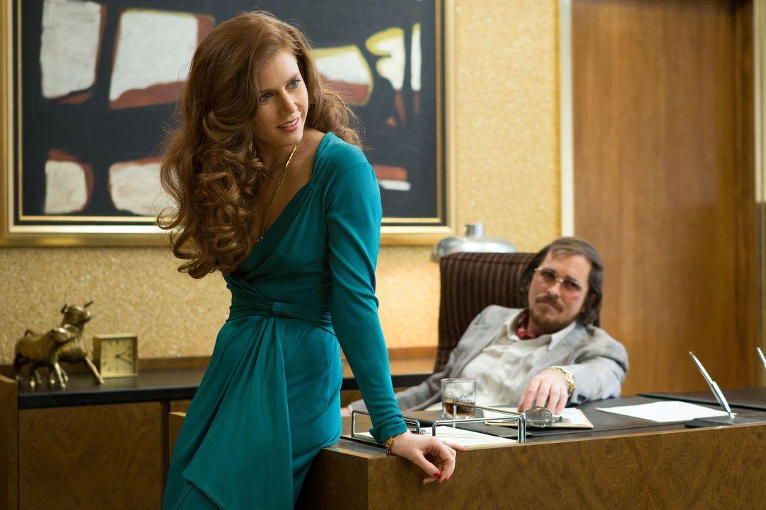 Ziehen bei ihren Kreditbetrügereien eine perfekte Show ab, der beinahe jeder auf den Leim geht: Irving (Christian Bale, r.) und seine Freundin Sydne... - Bildquelle: TOBIS TFILM