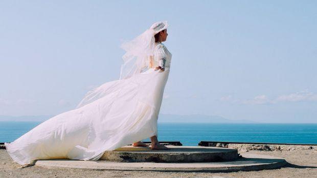 Auch ein Hut kann zum Brautkleid kombiniert werden.