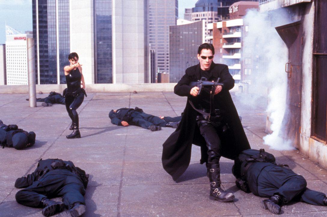 Allein gegen alle: Auch auf dem Dach werden Neo (Keanu Reeves, r.) und Trinity (Carrie-Anne Moss, l.) von Polizisten erwartet. - Bildquelle: Warner Bros. Pictures