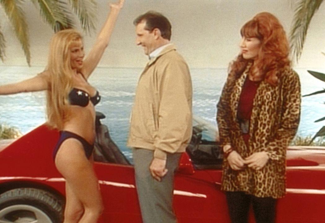 Eine knusprige Bikinidame präsentiert Al (Ed O'Neill, M.) und Peggy (Katey Sagal, r.) den Hauptgewinn: einen rasanten Sportwagen. - Bildquelle: Sony Pictures Television International. All Rights Reserved.