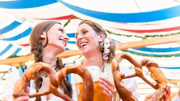 zwei Frauen im Festzelt mit geflochtenen Zöpfen halten große Brezeln in der Hand