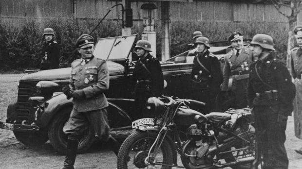 Im November 1937 verkündet Adolf Hitler (l.) seinen Generälen seine geheimen...