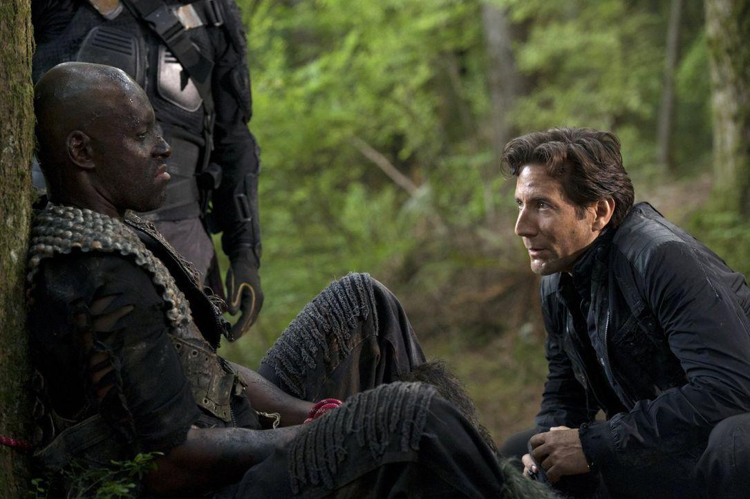 Kane (Henry Ian Cusick, r.) versucht mit Hilfe von Rivo (Colin Lawrence, l.) Frieden mit den Grounders zu schließen. Doch ist ein Gefangener wirklic... - Bildquelle: 2014 Warner Brothers