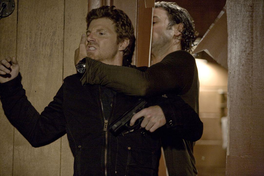 Mick (Alex O'Loughlin, hinten) ist sich sicher, dass ein Maulwurf (James C. Victor, vorne) für die die zwei ermordeten Polizisten verantwortlich ist... - Bildquelle: Warner Brothers