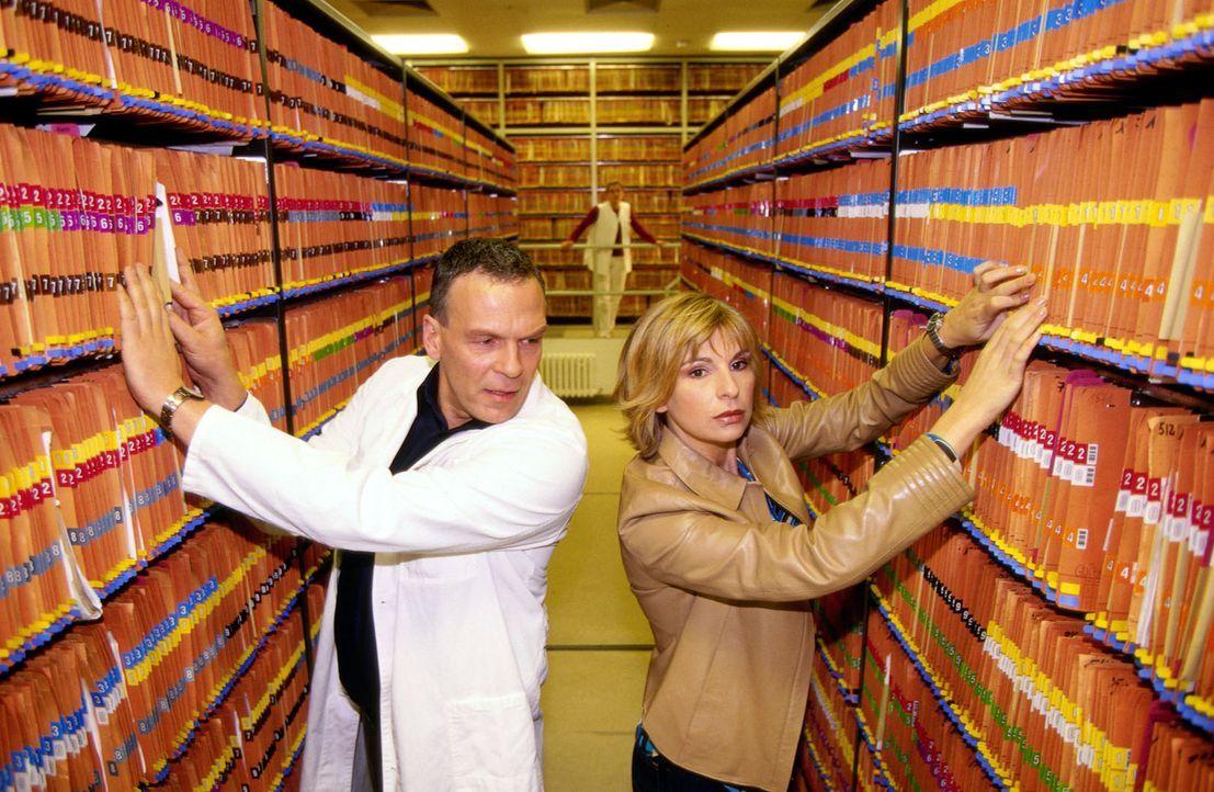 Dr. Zimmermann (Matthias Dittmer, l.) und Dr. Sommer (Maria Bachmann, r.) suchen fieberhaft die Akte von der Frau des Geiselnehmers, die bei der Ope... - Bildquelle: Uwe Ernst Sat.1