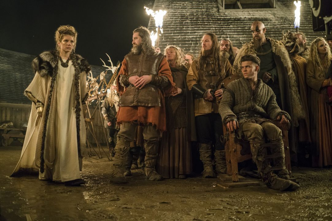 Die große Opferzeremonie beginnt: Lagertha (Katheryn Winnick, l.), Ivar (Alex Høgh Andersen, vorne), Floki (Gustaf Skarsgård, 7.v.r.) und Helga (Mau... - Bildquelle: 2016 TM PRODUCTIONS LIMITED / T5 VIKINGS III PRODUCTIONS INC. ALL RIGHTS RESERVED.