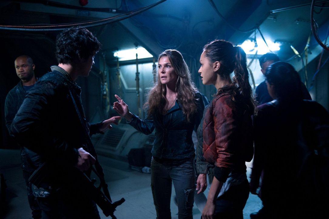 Bellamy (Bob Morley, 2.v.l.) und Raven (Lindsey Morgan, r.) sind sich nicht sicher, ob sie Abi (Paige Turco, M.) in Finns Fall noch trauen können ... - Bildquelle: 2014 Warner Brothers