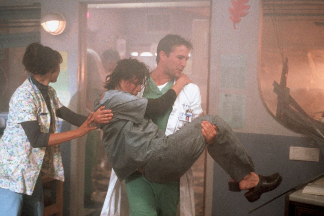 Freigesetzter Äther hat zu einer Explosion geführt. John Carter (Noah Wyle, M.) bringt Abby (Maura Tierney, M. vorne) in Sicherheit. - Bildquelle: TM+  2000 WARNER BROS.