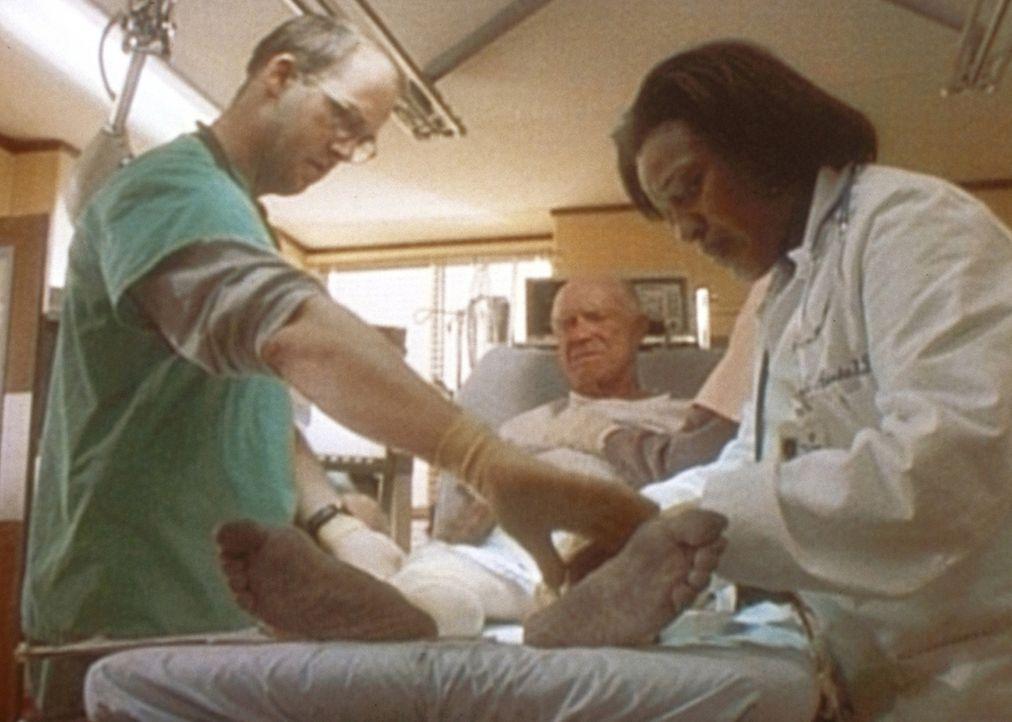 Dr. Greene (Anthony Edwards, l.) und Dr. Hicks (C. C. H. Pounder, r.) untersuchen einen Obdachlosen, der unter Erfrierungen leidet. - Bildquelle: TM+  WARNER BROS.