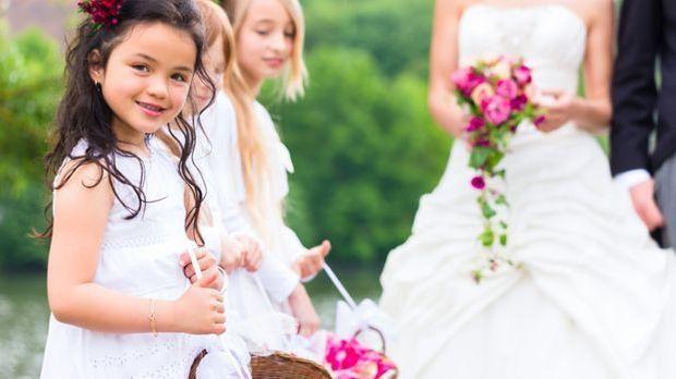 Blumenkinder bereiten den Weg für das frisch vermählte Brautpaar.