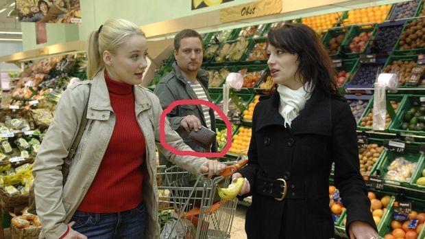 Geschickt lenken Lars (M.) und Agnieszka (l.) eine Frau am Gemüsestand ab, um...