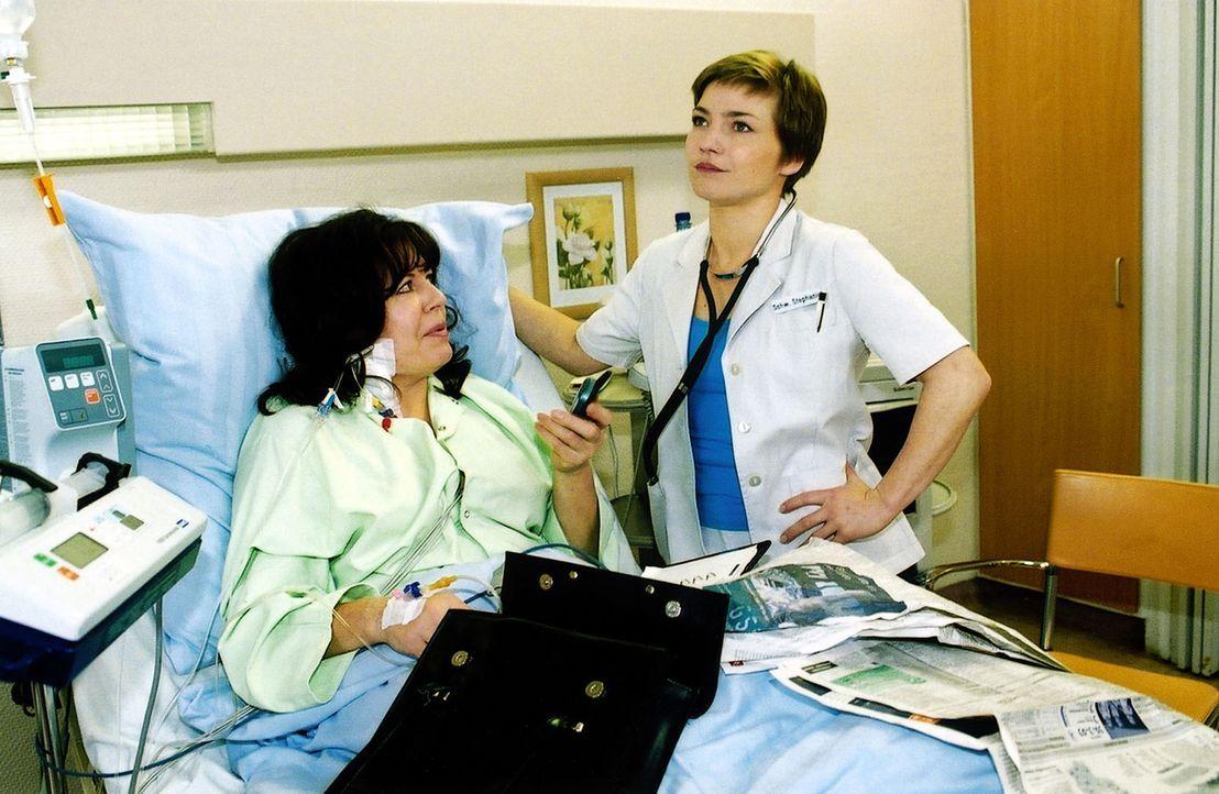 Stephanie (Claudia Schmutzler, r.) ist sichtlich genervt von der Patientin Brunhilde Maurer (Gundi Ellert, l.), die das Krankenzimmer zu ihrem Büro... - Bildquelle: Monika Schürle Sat.1