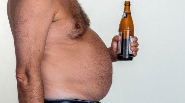 Mann mit Bierbauch und einer Bierflasche in der Hand