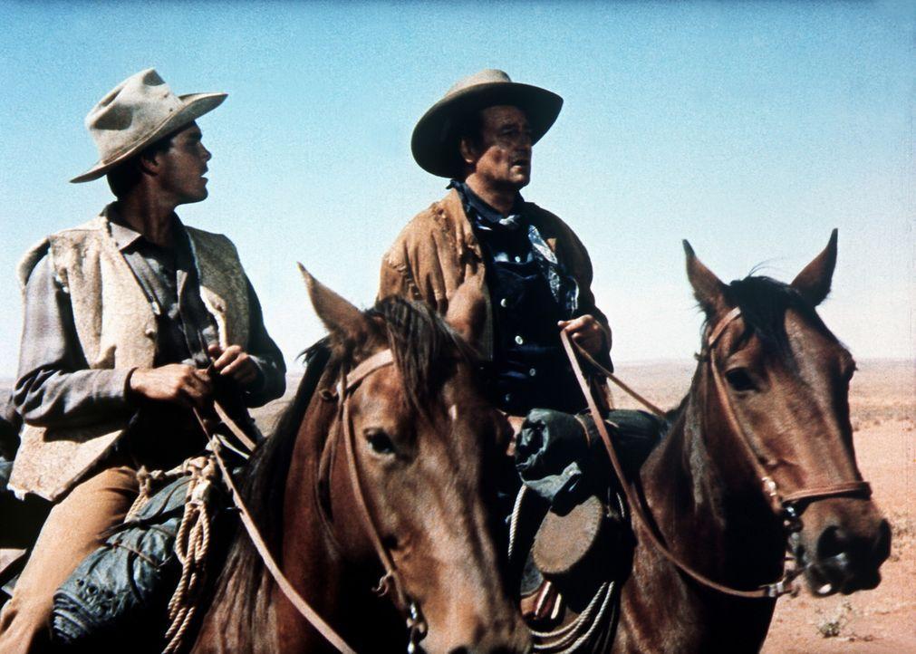 Schon fünf Jahre lang suchen Ethan (John Wayne, l.) und Martin (Jeffrey Hunter, r.) nach Ethans Nichte Debbie ... - Bildquelle: Warner Bros.