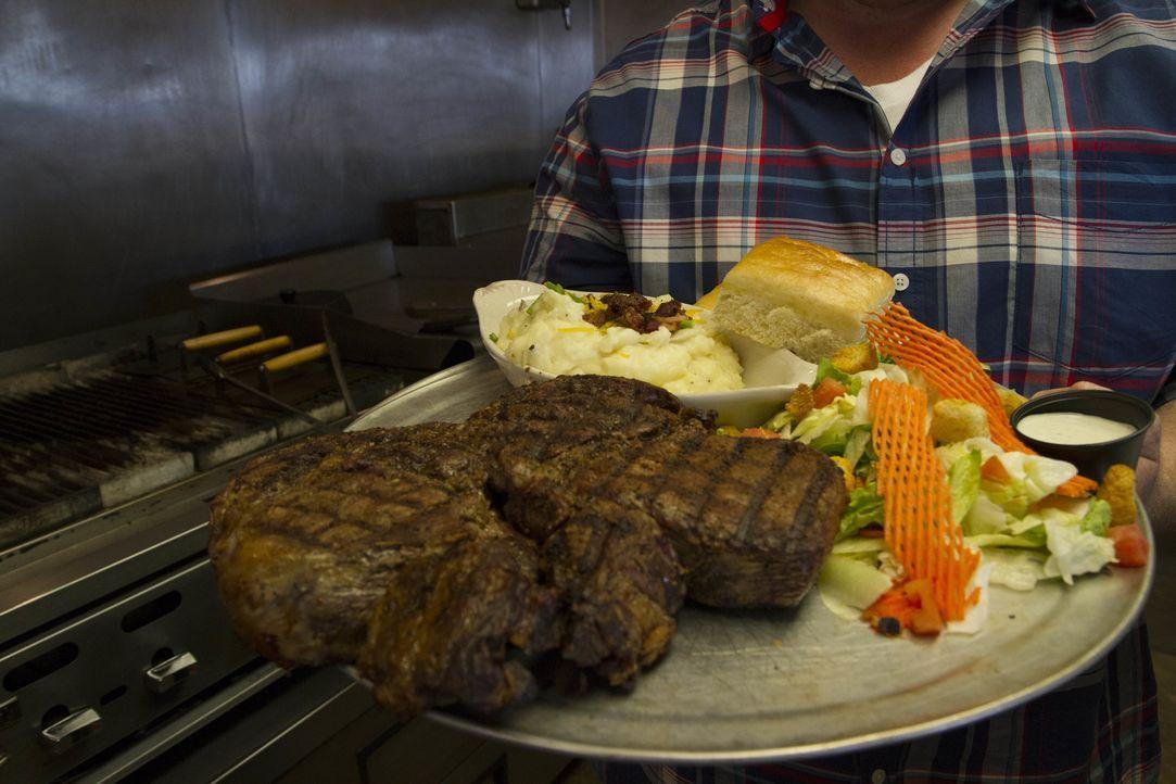 """Im """"Bull Mountain Grille"""" in Billings erwartet Casey Webb dieses Mal eine gigantische Steak-Challenge: ein 78-Unzen Rib Eye mit zwei Pfund Kartoffel... - Bildquelle: 2017,The Travel Channel, L.L.C. All Rights Reserved."""