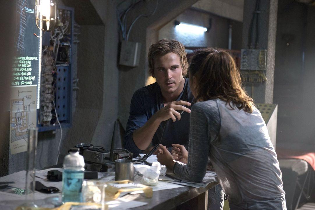 """Bellamy wartet in """"Mount Weather"""" auf Instruktionen von Raven (Lindsey Morgan, r.), doch diese sucht zusammen mit Wick (Steve Talley, l.) immer noch... - Bildquelle: 2014 Warner Brothers"""