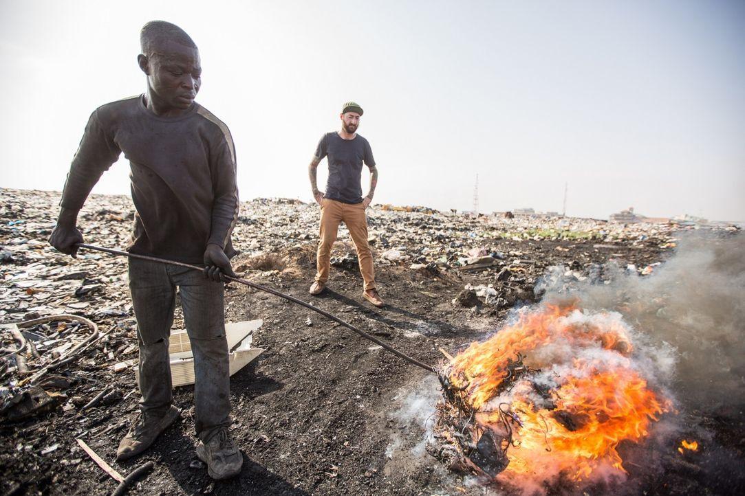Reporter Oliver Plöger (r.) blickt hinter die Kulissen der Elektroschrottdeponie von Agbogbloshie in Ghana, auf und vor der knapp 50.000 Menschen le... - Bildquelle: ProSieben MAXX