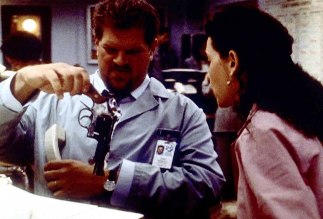 Hathaway (Julianna Margulies, r.) bittet Jerry (Abraham Benrubi, l.), die Waffe eines psychisch labilen Patienten wegzuschließen, der damit seine F... - Bildquelle: TM+  2000 WARNER BROS.