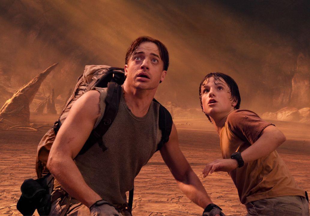 Werden von einem aufgebrachten Giganotosaurus angegriffen: Trevor Anderson (Brendan Fraser, l.) und sein 13-jähriger Neffe Sean (Josh Hutcherson, r... - Bildquelle: Warner Bros.