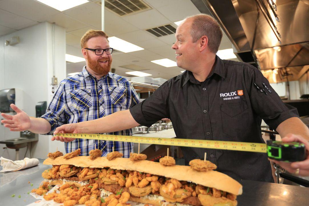 """Koch Jason (r.) misst für Josh (l.) gerne noch einmal nach: das """"BL-Titan Sandwich"""" erstreckt sich tatsächlich über einen ganzen Meter. - Bildquelle: 2017,Television Food Network, G.P. All Rights Reserved"""
