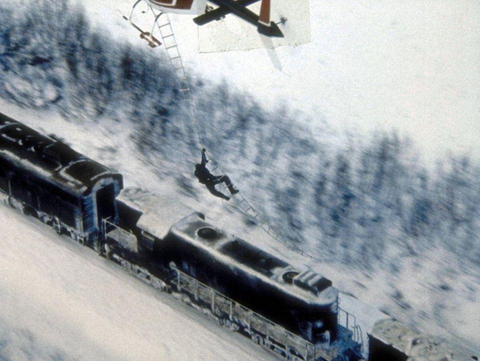 Der sadistische Gefängnisdirektor Ranken (John P. Ryan) seilt sich von einem Hubschrauber auf den fahrenden Zug ab, um Rache zu üben. - Bildquelle: Cannon Releasing Corp.